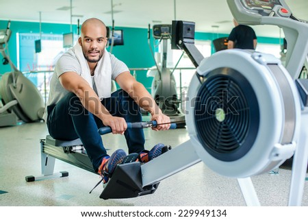 Portrait of an athlete during training. Confident exercise on rowing machine. Young man at the gym on rowing machine in full force. - stock photo