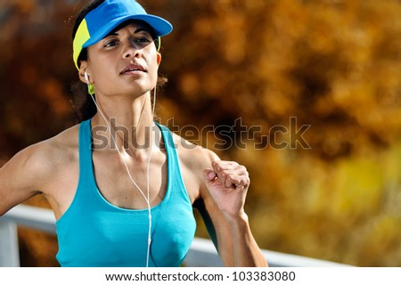 portrait of an athlete running outdoors with headphones and autumn leaves. wellness, fitness exercise woman training - stock photo