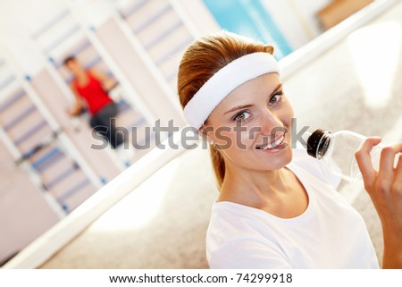 Portrait of an athletic woman taking a drink in gym - stock photo