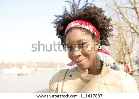 Portrait of an attractive african american woman sightseeing in London's river Thames while on vacation, smiling.