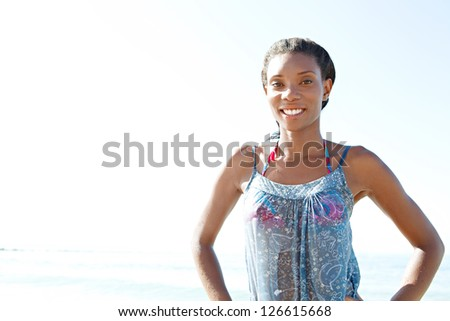 "Portrait of an attractive ""african american"" woman standing by the sea and smiling against a bright blue sky while on a beach vacation. - stock photo"