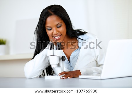 Portrait of an attractive african woman working with a microscope and a laptop at soft colors composition - stock photo