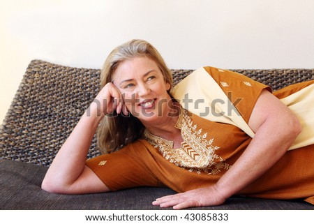 Portrait of an attractive and happy mature woman relaxing at home.