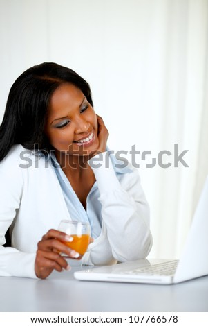 Portrait of an attractive and relaxed woman reading on laptop screen at soft colors composition - stock photo