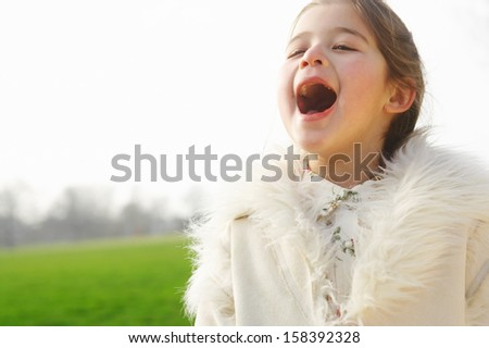 Portrait of an attractive and talented young child girl singing aloud voice while standing in a green grass field if a park during a sunny winter day, outdoors. - stock photo