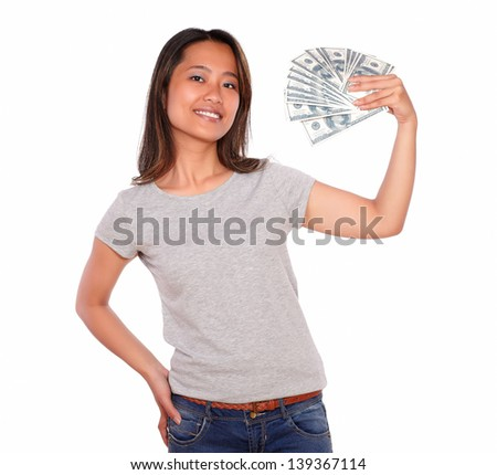 Portrait of an attractive asiatic young woman holding cash money while is looking at you against white background