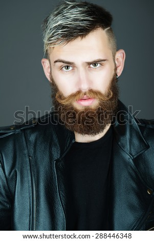 Portrait of an attractive bearded man in a studio in a black leather jacket on a dark background