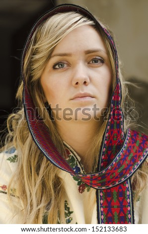 Portrait of an attractive beautiful girl in traditional ukrainian cloth on old ruin concrete background