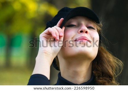 Portrait of an attractive beautiful pretty cute young caucasian cheerful smiling woman (girl, female, person, model) dressed in a black peak cap, holding it by hand and looking straight forward at you - stock photo
