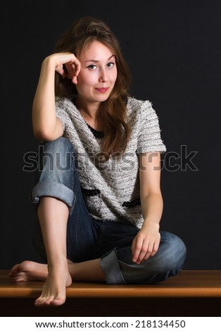 Portrait of an attractive beautiful pretty cute young caucasian woman (lady, girl, female, person, model) sitting in cross-legged pose, staring at you and smiling. Dark background. - stock photo
