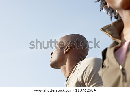 Portrait of an attractive black couple against a blue sky. - stock photo