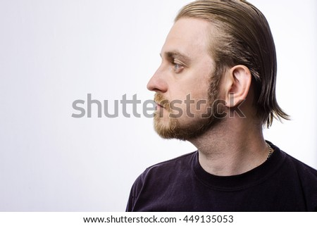 Portrait of an attractive blond hipster beard in profile on a gray background