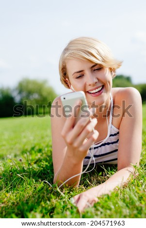 Portrait of an attractive blond woman with earphones lying on the grass