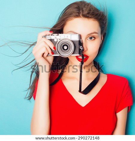Portrait of an attractive brunette woman in a red dress in the studio on a blue background with a camera in his hands - stock photo