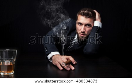 Portrait of an attractive business man with a cigar and a glass of whiskey