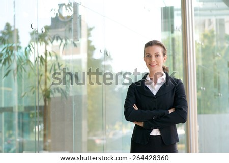 Portrait of an attractive business woman smiling with arms crossed outside of office building