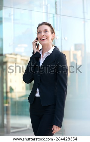 Portrait of an attractive business woman walking and talking on cell phone  - stock photo