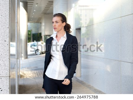 Portrait of an attractive business woman walking outside - stock photo