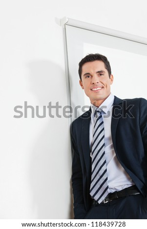 Portrait of an attractive businessman leaning on a white office wall - stock photo