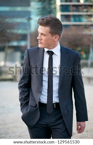 Portrait of an attractive businessman walking in the city - stock photo