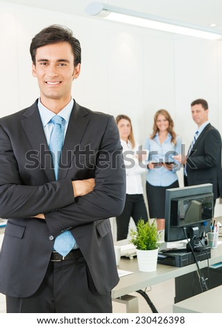 Portrait of an attractive businessman with his colleagues in the background - stock photo