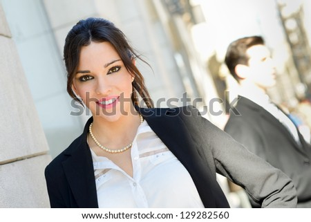Portrait of an attractive businesswoman standing outside of company building. Couple working. - stock photo