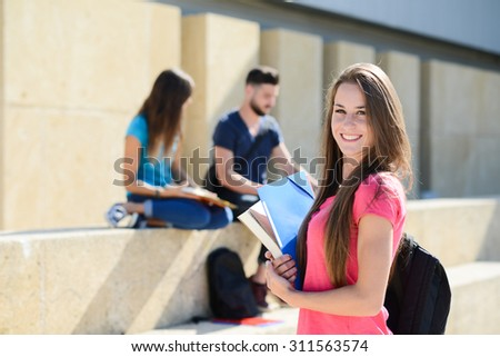 portrait of an attractive cheerful young student woman outdoor in front of high school campus - stock photo