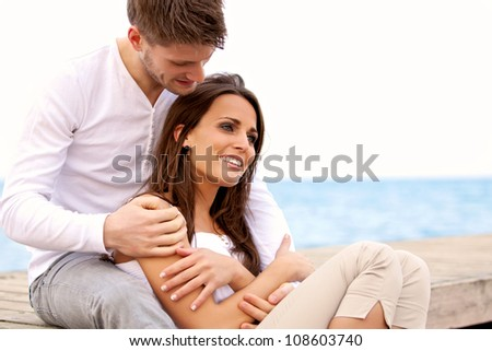 Portrait of an attractive couple enjoying each other's company by the sea - stock photo