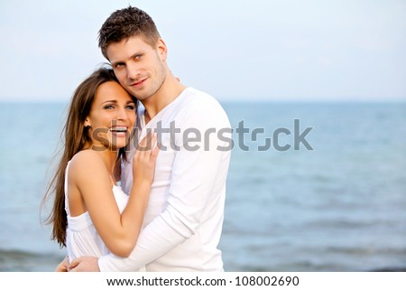 Portrait of an attractive couple enjoying the beach - stock photo