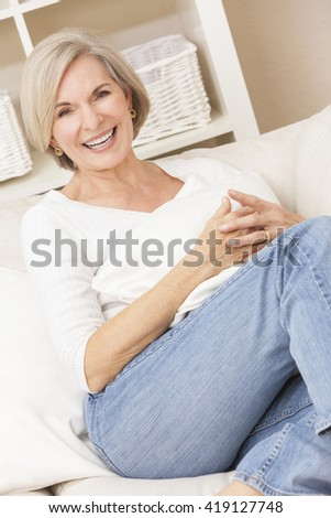 Portrait of an attractive elegant senior woman wearing jeans and relaxing at home on her sofa - stock photo