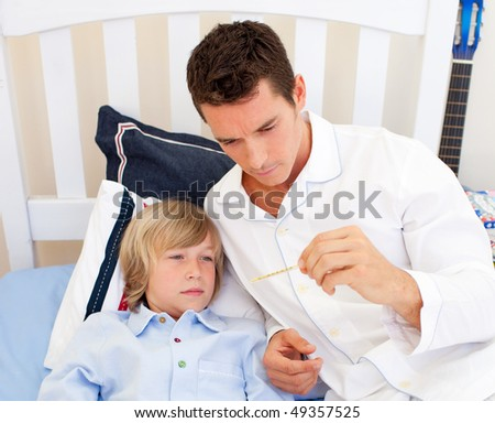 Portrait of an attractive father checking his son's temperature in the bedroom