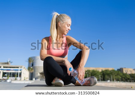 Portrait of an attractive female jogger with cute smile enjoy rest after workout against blue sky with copy space for your text message or content, young fit woman in sportswear taking break after run - stock photo
