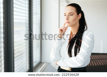 Portrait of an attractive female manager standing and thinking by a window