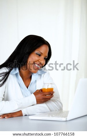 Portrait of an attractive female reading on laptop screen while is drinking an orange juice at soft composition - stock photo