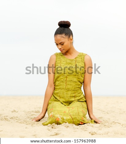 Portrait of an attractive female sitting at the beach and meditating - stock photo