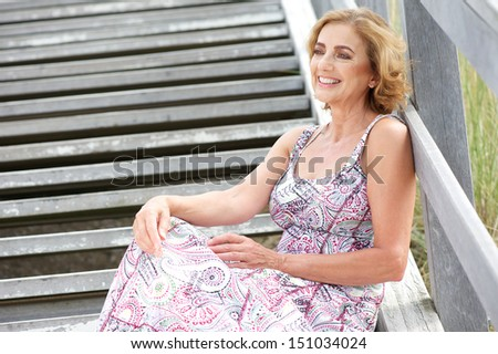 Portrait of an attractive female sitting on stairs outdoors with happy expression - stock photo