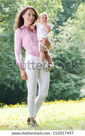 Portrait of an attractive female smiling and holding baby in the park