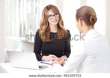 Portrait of an attractive financial officer businesswoman sitting in front of laptop and consulting with professional investment advisor.