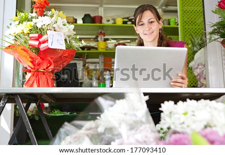 Portrait of an attractive florist business woman owner sitting at a flower shop counter using a laptop computer to place a stock order on line, smiling. Small business technology. - stock photo