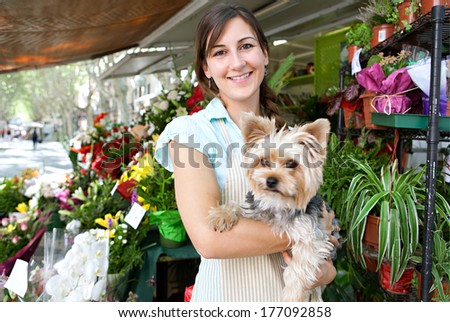 Portrait of an attractive florist kiosk business owner standing in her flower market stall shop, carrying her dog pet and smiling at the camera during a sunny day. Running a small business. - stock photo
