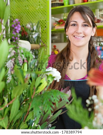 Portrait of an attractive, friendly and joyful florist business woman owner working and making a new floral arrangement in her flower shop. Small business owner.