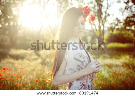 Portrait of an attractive girl in a poppy field at sunset - stock photo