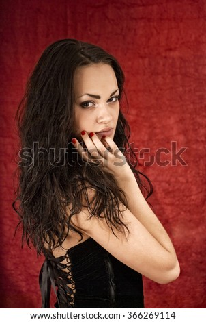 portrait of an attractive girl in black on a red background