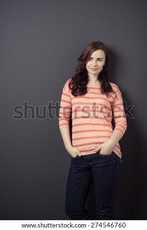 Portrait of an Attractive Girl in Trendy Attire Leaning on Gray Wall with Both Hands in the Pocket. - stock photo