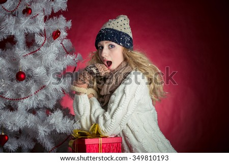 Portrait of an attractive girl in winter clothes with gifts for Christmas