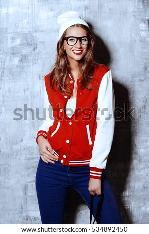 Portrait of an attractive girl with bright red lips wearing modern clothes. College, school style. Hipster. Youth fashion.