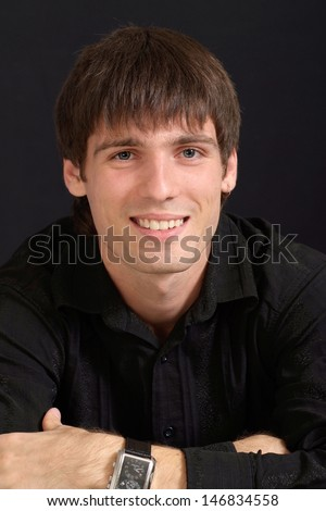 Portrait of an attractive guy in a black shirt on a black background