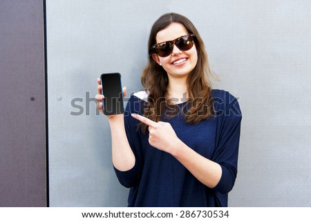 Portrait of an attractive happy brunette young woman wearing sunglasses and pointing to her smart mobile phone, on grey background - stock photo