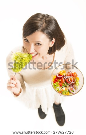 Portrait of an attractive happy young woman eating vegetables salad, studio shot on white background. Healthy food concept.