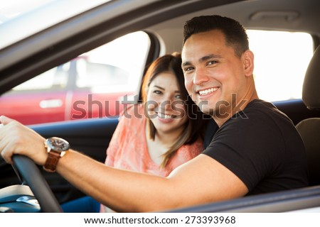 Portrait of an attractive Hispanic couple driving a car and about to go on a trip - stock photo